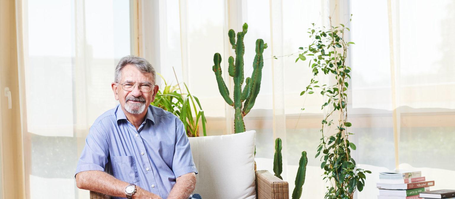 Dr. med. Rudolph Stäubli sitzt auf einem Stuhl in einer hellen Arztpraxis.